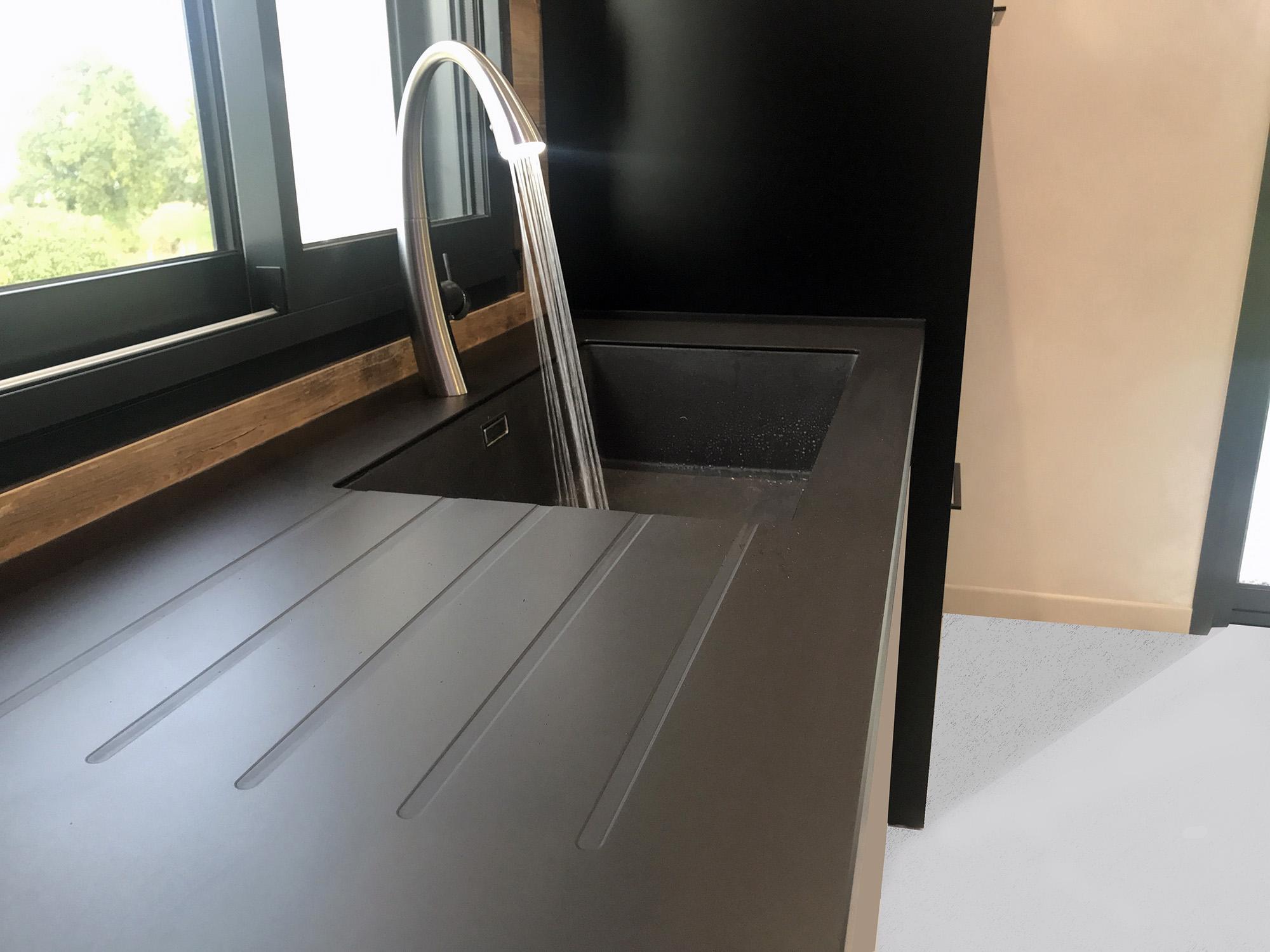 evier en céramique noire de la couleur du plan de travail avec mitigeur led integrée