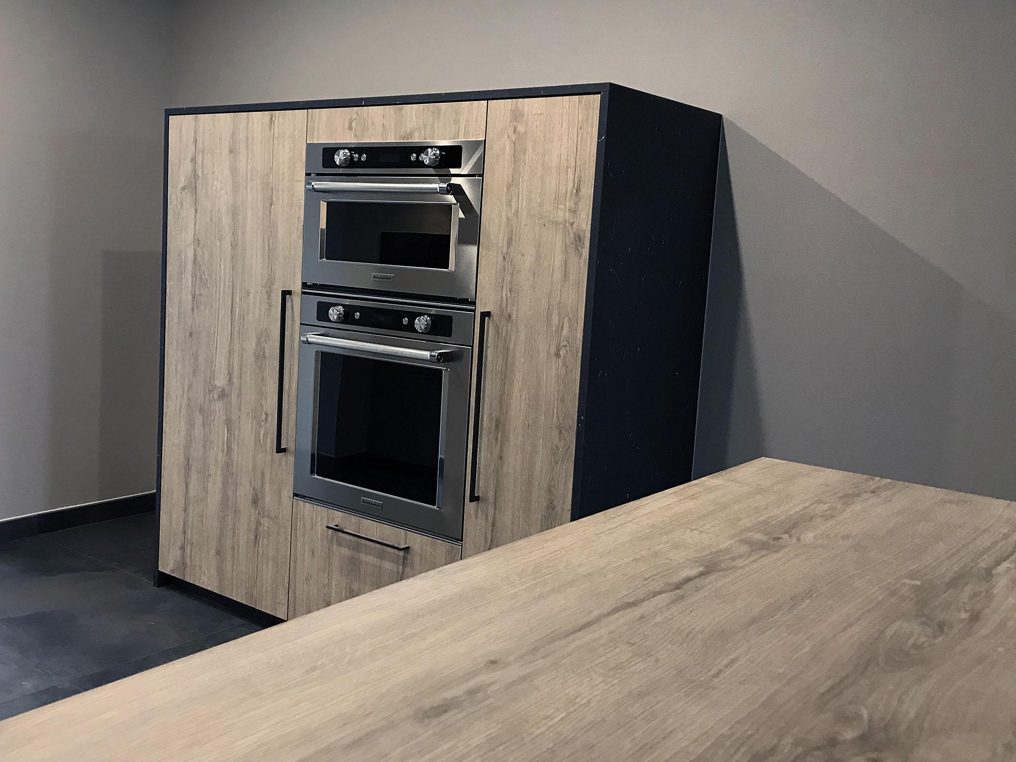 deux fours kitchenaid l'un au dessus de l'autre dans un meuble indépendant bois vieilli entouré de stratifié noir