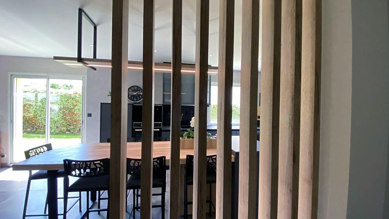 Cloison ajourée en stratifié finition chêne pour séparer la salle de l'entrée