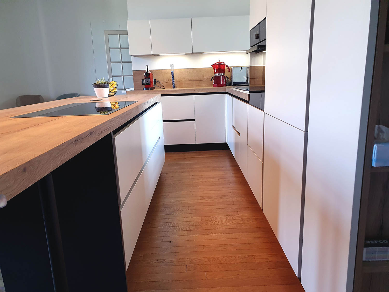 Cuisine blanche et ilot  avec tiroirsblanche et plan de travail bois à nœuds avec sol parquet chêne