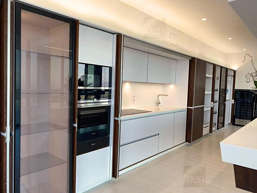 La cuisine est cachée derrière les façades en Noyer. Les portes s'encastrent sur le côté des meubles de cuisine