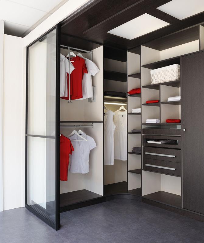 Grand dressing en U avec trois penderies tiroirs spécifiques avec vue (façade verre), l'éclairage design est assuré par des LED derrière un panneau de bois et de verre (éclairage indirecte)
