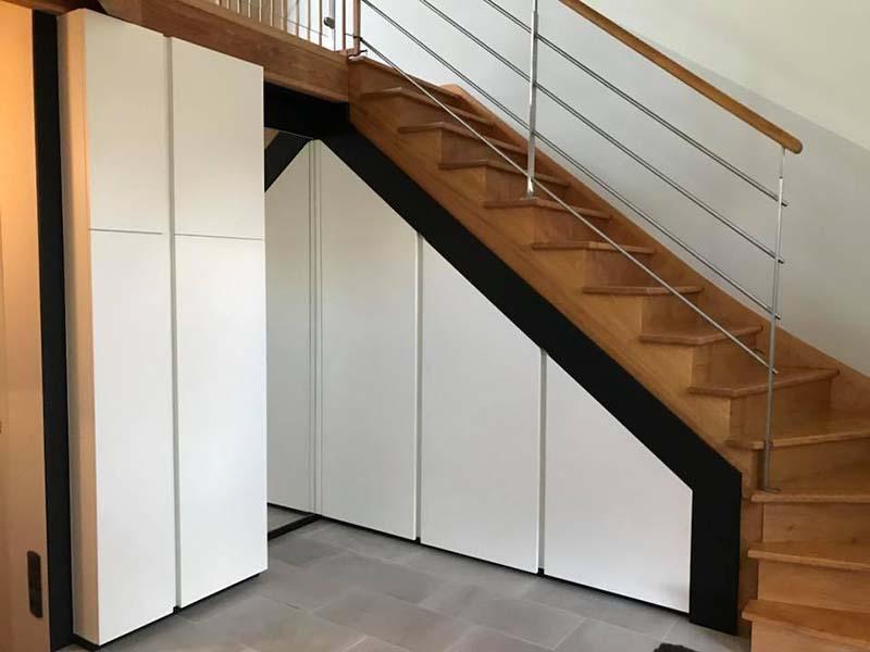Aménagement de placards sous escalier, de couleur noir et blanc