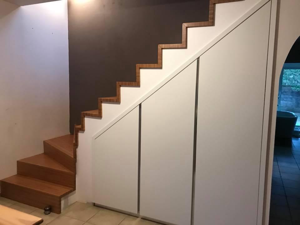 placard sous escalier en biseau avec passage en arche vers la salle à manger
